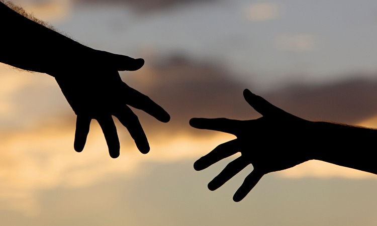 Two hands reach for each other against the sky